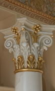 Close-up of gilded capital of white scagliola column